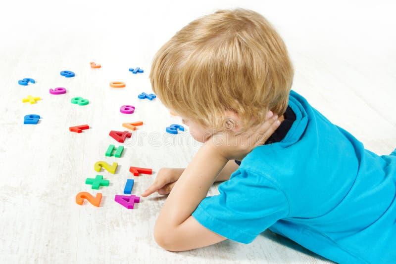 El niño soluciona el ejemplo de las matemáticas. Prueba fotos de archivo libres de regalías