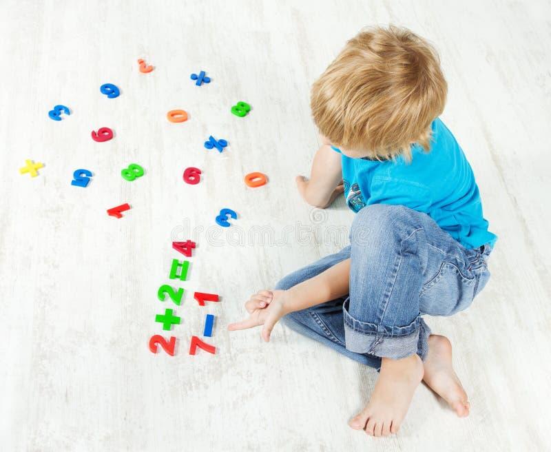 El niño soluciona el ejemplo de las matemáticas. Prueba foto de archivo libre de regalías