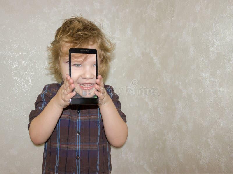 El niño sonríe en la cámara y toma un selfie fotos de archivo