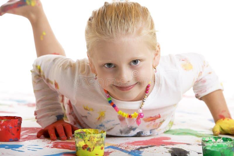 El niño sonríe feliz durante la sesión de la pintura imagenes de archivo