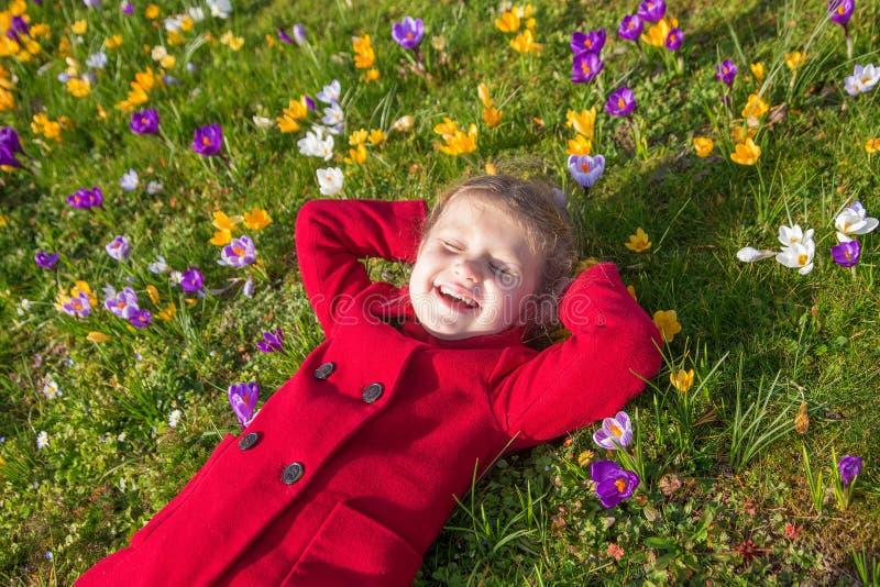 El niño sonriente está mintiendo entre las azafranes de las flores de la primavera fotos de archivo libres de regalías