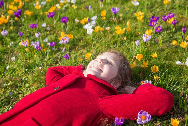 El niño sonriente está mintiendo entre las azafranes de las flores de la primavera imagenes de archivo