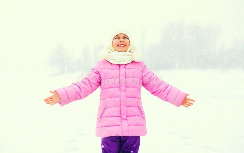 El niño sonriente feliz de la niña del invierno goza de los copos de nieve en nieve imagen de archivo libre de regalías