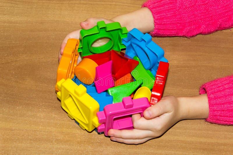 El niño sostiene los juguetes de las unidades de creación en sus manos y hace la cama Las unidades de creación juegan para los ni fotos de archivo libres de regalías