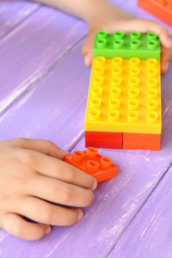 El niño sostiene los juguetes de las unidades de creación en sus manos y juegos Las unidades de creación de los niños fijaron que imagen de archivo