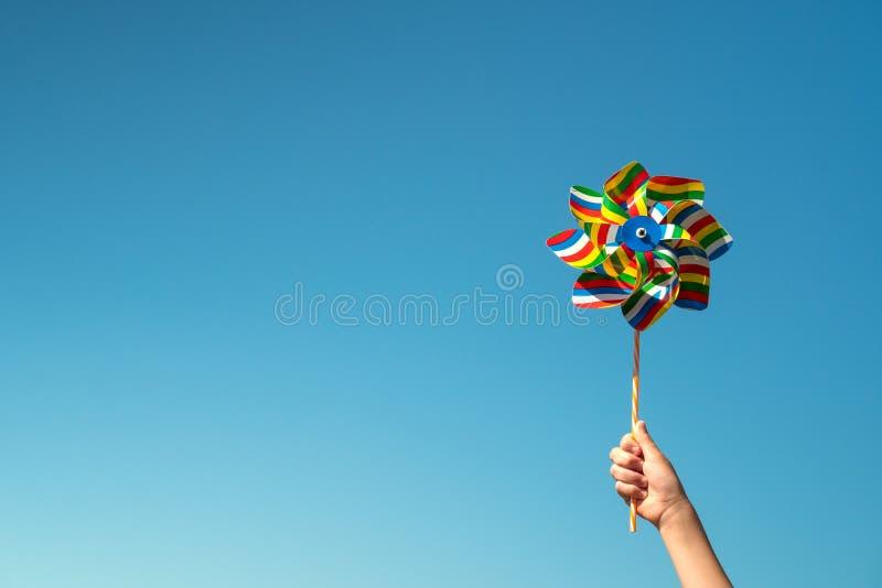 El niño sostiene el molinillo de viento colorido foto de archivo libre de regalías