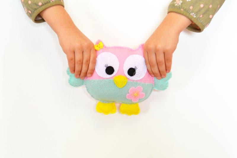El niño sostiene un juguete del búho en sus manos Juegos de niños con un juguete suave Juguete divertido del búho del fieltro imagen de archivo