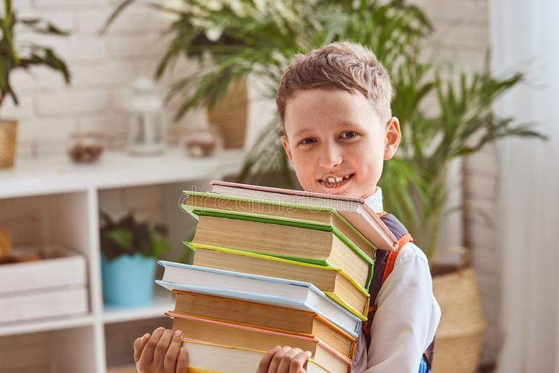 El niño sostiene una pila de libros de texto fotografía de archivo libre de regalías