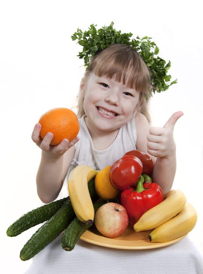 El niño sostiene vehículos y la fruta. imagenes de archivo