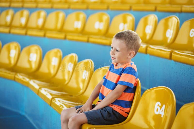 El niño toma para poseer el asiento en el p del estadio o del dolphinarium y el esperar imagen de archivo