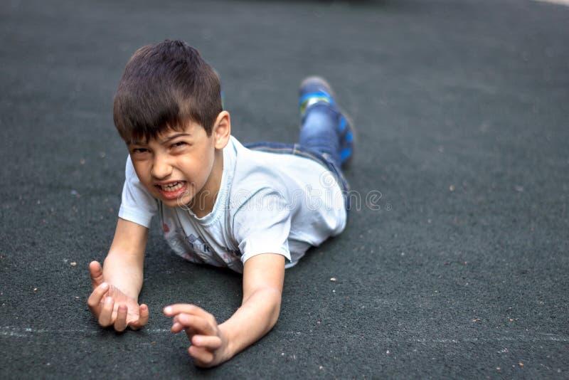 El niño tropezó y se cayó, golpeó su mano, el muchacho tropezó y se cayó en la acera He& x27; daño de s fotos de archivo