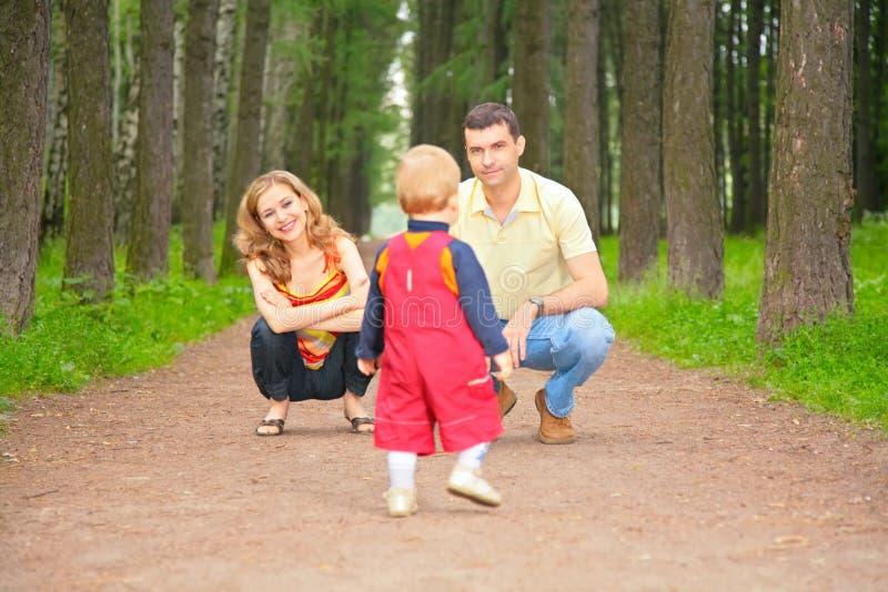El niño va en pista a los padres fotografía de archivo