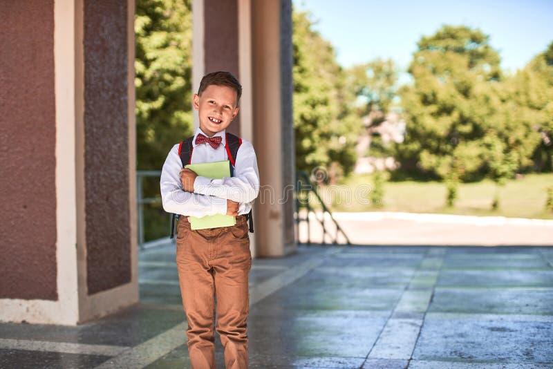 El niño va a la escuela primaria retrato de un niño feliz con una cartera en el suyo detrás fotos de archivo