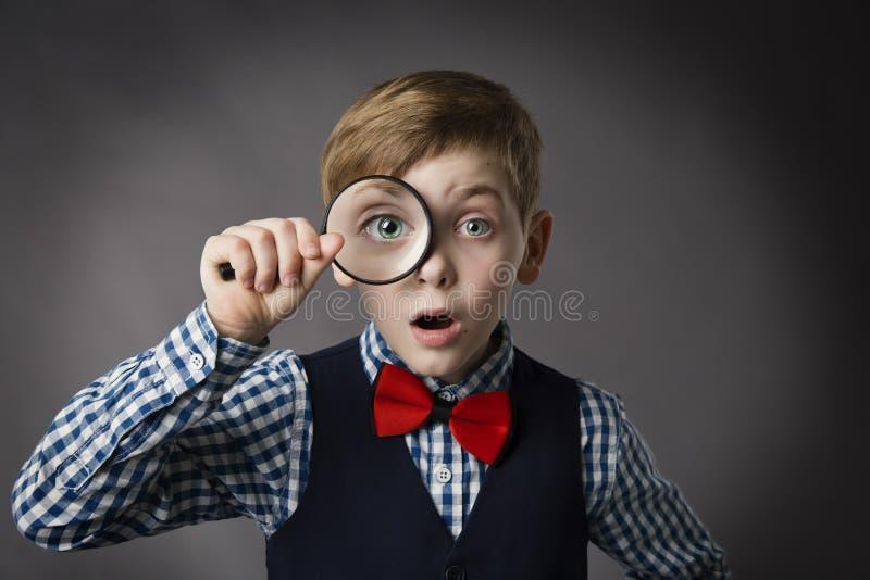 El niño ve a través la lupa, lente de la lupa del ojo del niño fotografía de archivo
