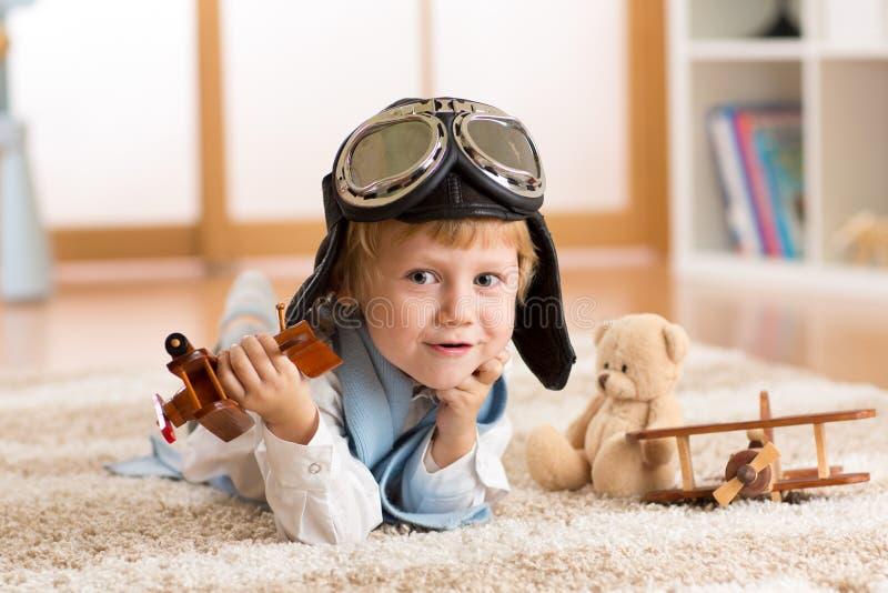 El niño weared juegos del piloto o del aviador con un aeroplano del juguete en casa en sitio del cuarto de niños Concepto de sueñ fotos de archivo libres de regalías