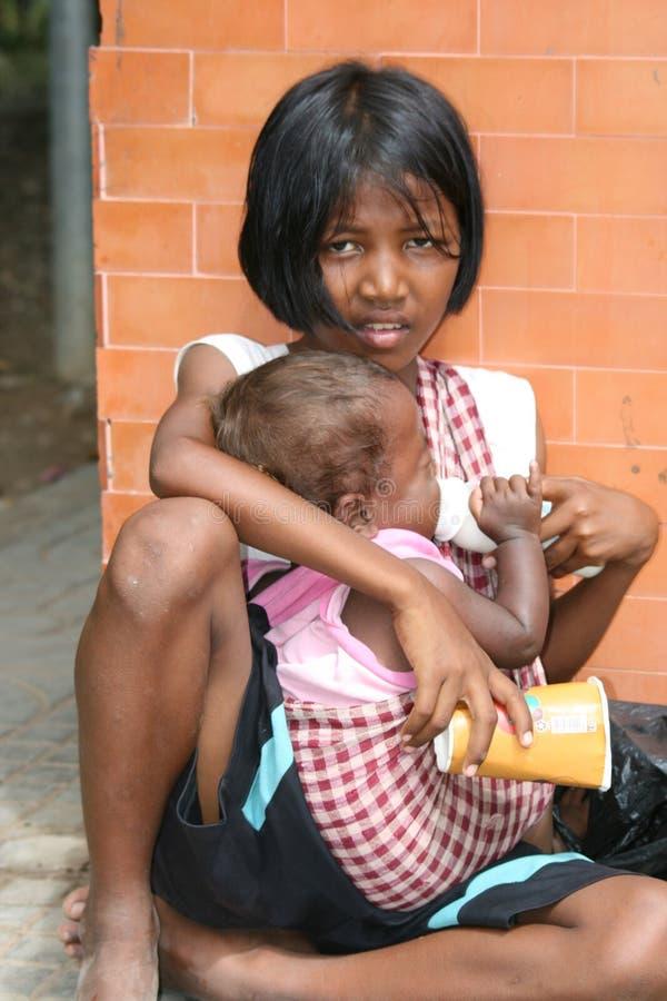 El niño y el bebé sientan el petición dinero en Camboya. foto de archivo libre de regalías