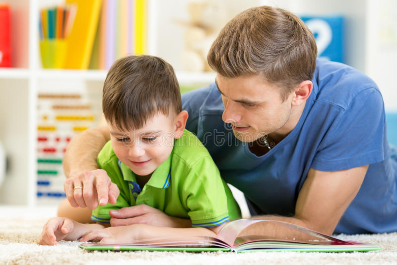 El niño y el padre leyeron un libro en piso en casa foto de archivo libre de regalías