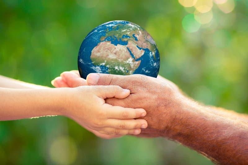 El niño y el sostenerse mayor conectan a tierra el planeta en manos foto de archivo libre de regalías