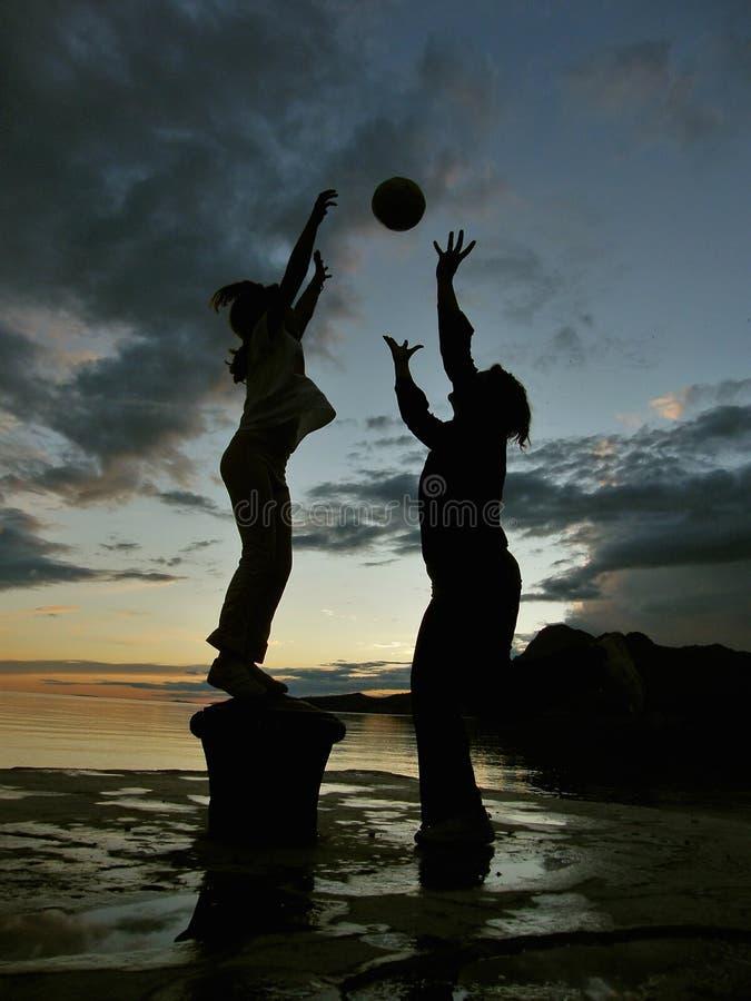El niño y la madre juegan con la bola en la puesta del sol 1 fotos de archivo libres de regalías