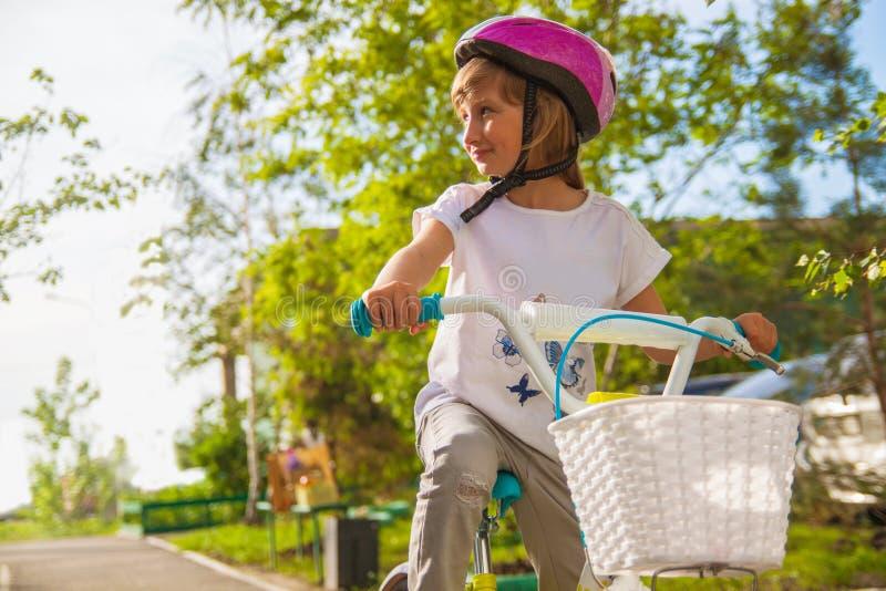 El ni?o en un casco que monta una bici en el parque Beb? hermoso foto de archivo libre de regalías