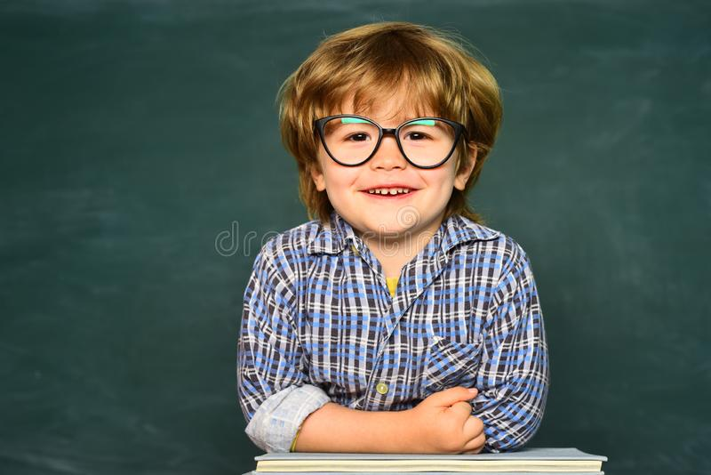 El ni?o est? aprendiendo en clase en el fondo de la pizarra Lectura de la mama con el hijo Ni?os felices de la escuela Proceso ed foto de archivo