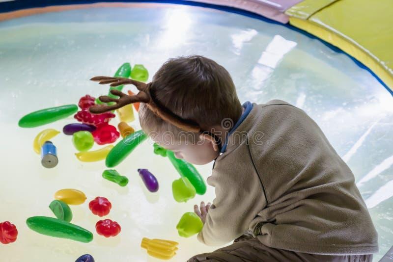 El ni?o feliz lindo, muchacho que juega en el juguete pl?stico colorido figura en patio fotografía de archivo