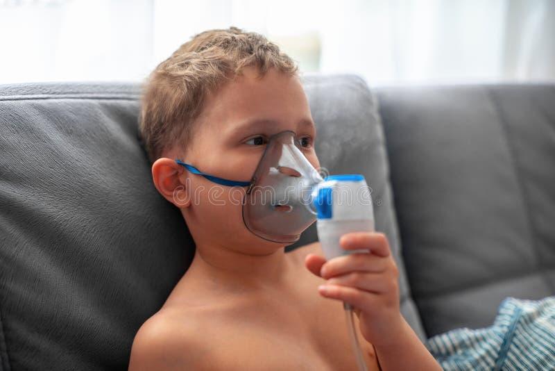 El ni?o hace el nebulizador de la inhalaci?n en casa en la cara llevar un nebulizador de la m?scara que inhalaba el vapor roci? l imagen de archivo libre de regalías