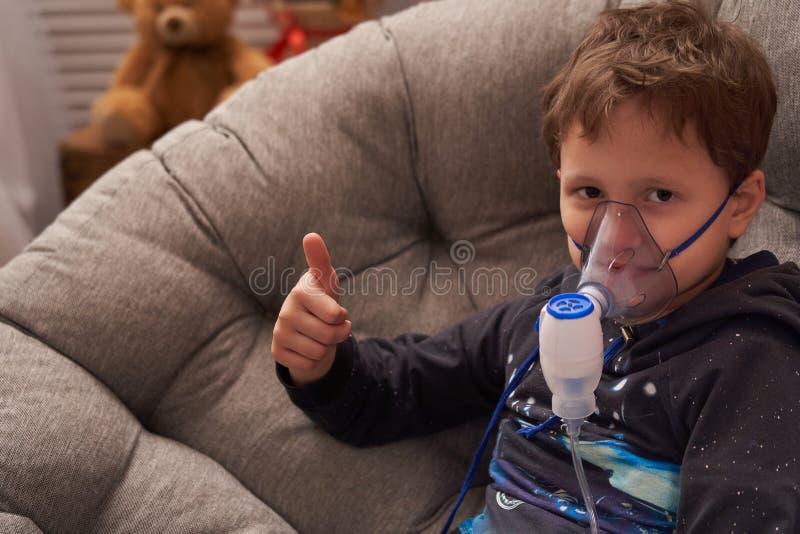 El ni?o hace el nebulizador de la inhalaci?n en casa en la cara llevar un nebulizador de la m?scara que inhalaba el vapor roci? l imágenes de archivo libres de regalías