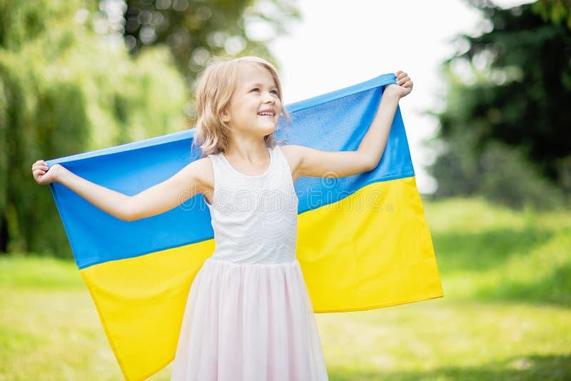 El ni?o lleva agitar bandera azul y amarilla de Ucrania en campo D?a de la Independencia del ` s de Ucrania D?a de indicador D?a  fotografía de archivo libre de regalías