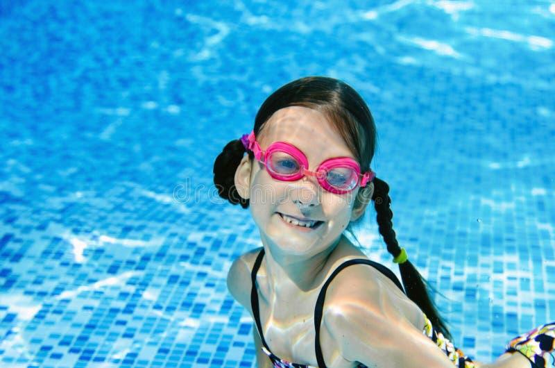 El ni?o nada bajo el agua en la piscina, zambullidas activas felices de la muchacha del adolescente y se divierte bajo el agua, l foto de archivo