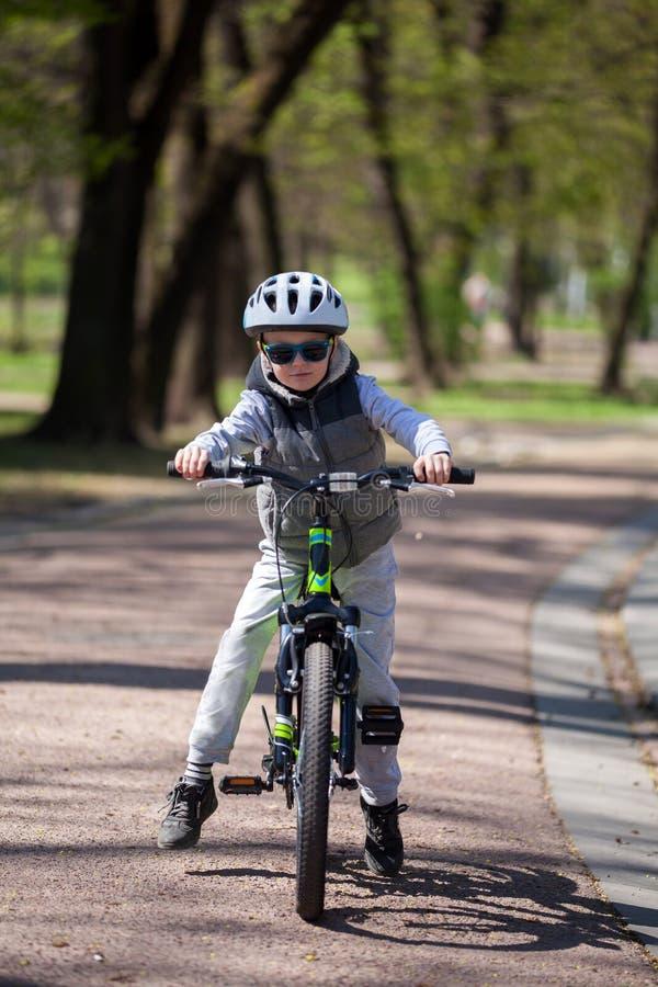 El ni?o peque?o aprende montar una bici en el parque El muchacho lindo en gafas de sol monta una bici Ni?o sonriente feliz en el  imagen de archivo libre de regalías