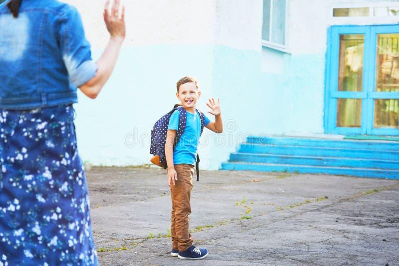 El ni?o va a la escuela el colegial del muchacho va a enseñar en la mañana niño feliz con una cartera en el suyo detrás y los lib imagen de archivo