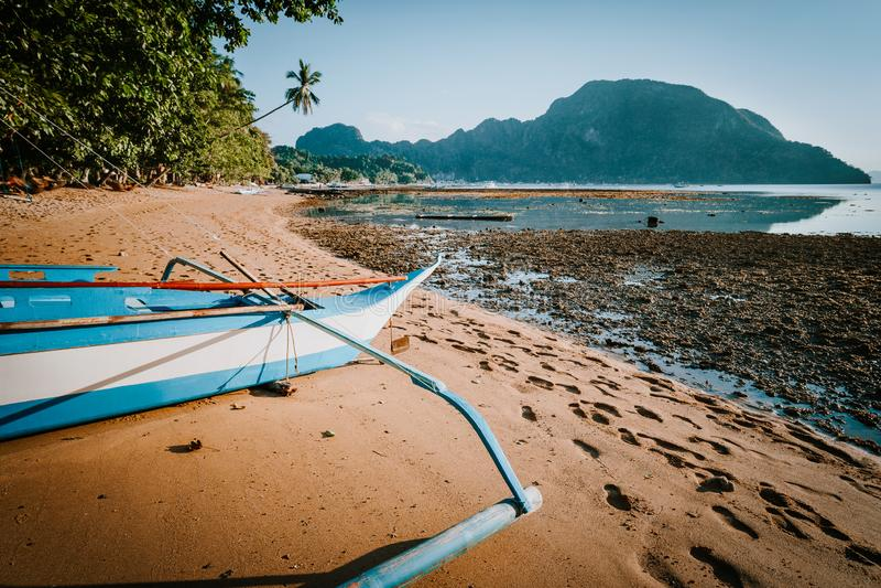 El Nido海湾看法与地方banca小船的在前面低潮中,美丽如画的风景下午,巴拉旺岛 库存图片