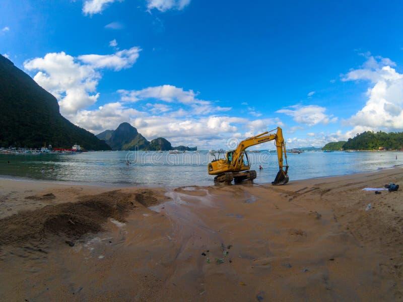 El Nido,菲律宾- 2018年11月21日:日落与挖掘机的海滩视图 清洗和修饰热带海边 免版税库存照片