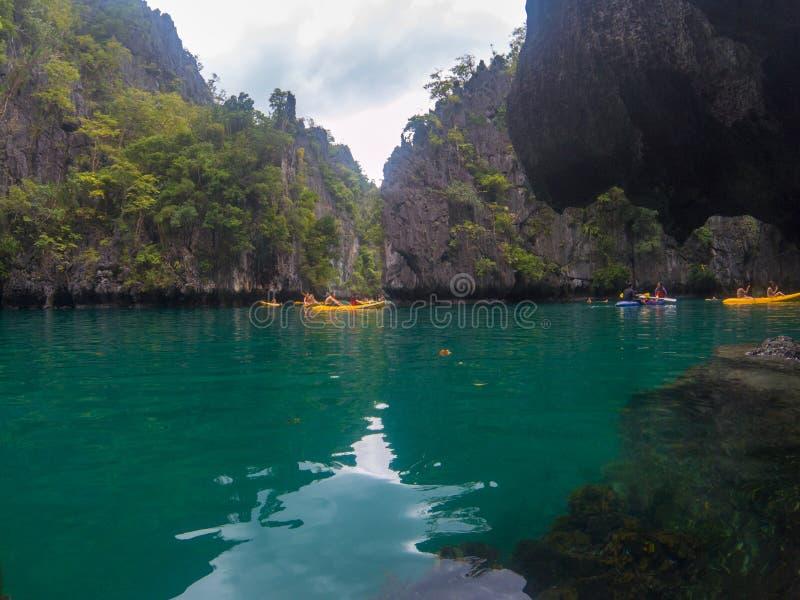 El Nido Filipiny - 20 2018 Nov: morze krajobraz z czerni skałą i turysta w kajaku Łódkowata wycieczka turysyczna wokoło Palawan obrazy royalty free