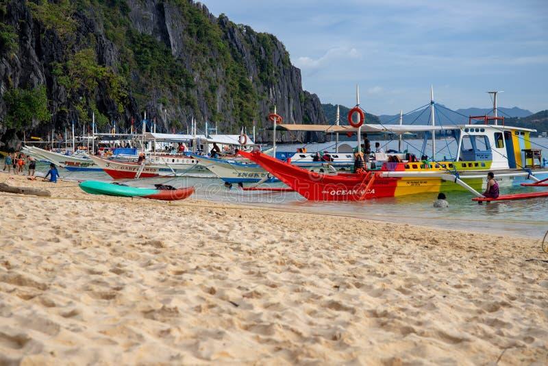El Nido, Filippinerna - 20 November 2018: havslandskap med färgrika fartyg och sandstranden Idyllisk strand för Palawan ö arkivfoto