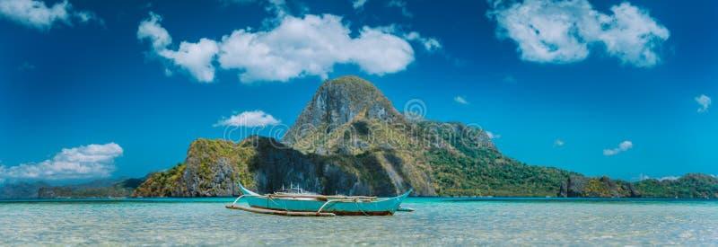 EL Nido, la barca dei pescatori in baia blu con la vista panoramica dell'isola di Cadlao nel fondo, Palawan, Filippine fotografie stock libere da diritti