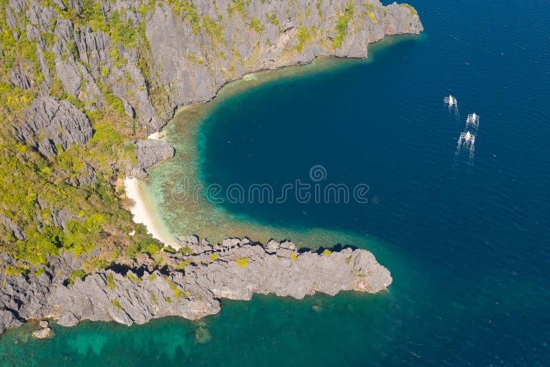 El Nido, Palawan, Filippinerna, flyg- sikt av fartyg och karstlandskap på den hemliga lagunstranden arkivbild