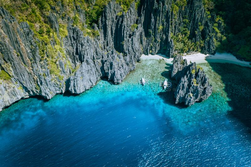 El Nido, Palawan, Philippines. Aerial above view of banca boats surrounded by karst scenery rocks at Secret Lagoon beach royalty free stock images