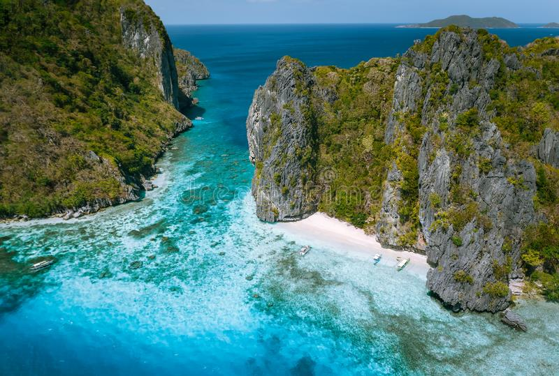 El Nido, Palawan, Philippines. Aerial view of tropical sea stack Island with tourist boats moored at white sandy beach.  stock photos