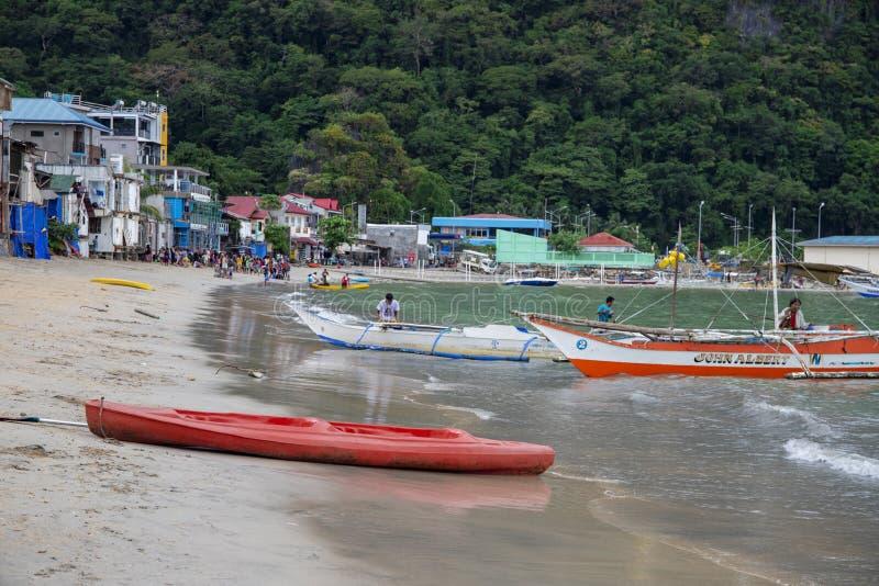 EL Nido, Philippines - 20 novembre 2018 : kayak rouge sur la plage de sable Bateau de touristes sur le rivage Bâtiments colorés d photo libre de droits