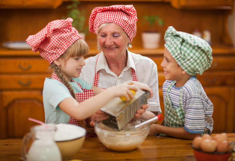 El nieto y la nieta besan a su abuela en la cocina imagen de archivo