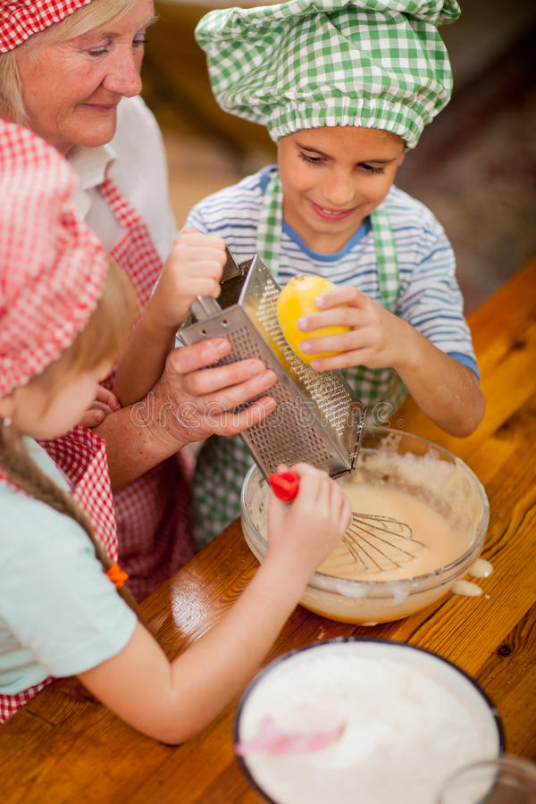 El nieto y la nieta besan a su abuela en la cocina imagenes de archivo