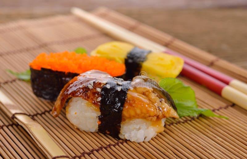 El nigiri y el sashimi del sushi sirvieron en la estera de bambú con los palillos en fondo de madera imágenes de archivo libres de regalías