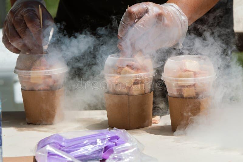 El nitrógeno líquido cuece al vapor mientras que el hombre prepara las invitaciones congeladas en el festival fotos de archivo