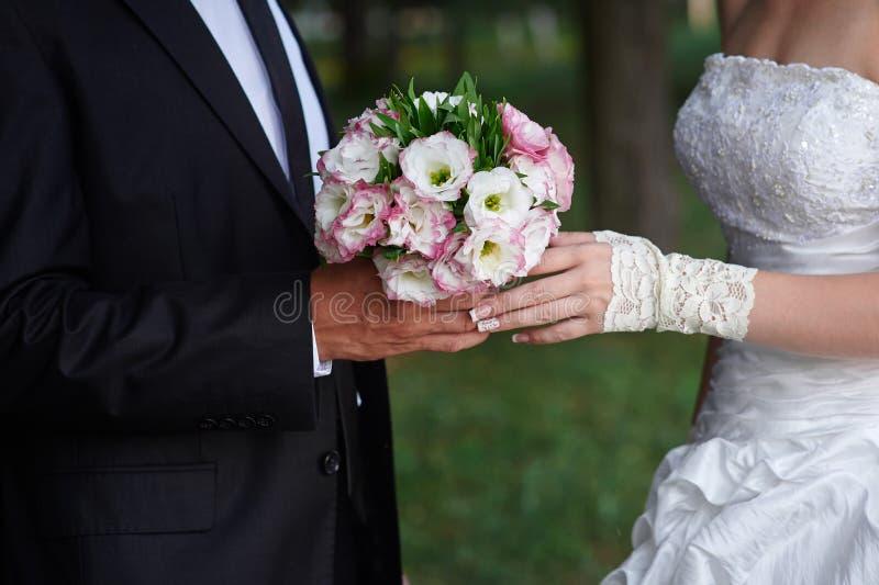 El novio abraza a la novia, y ella sostiene un ramo nupcial en sus manos fotos de archivo
