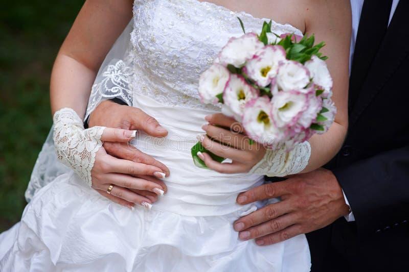 El novio abraza a la novia, y ella sostiene un ramo nupcial en sus manos imagen de archivo