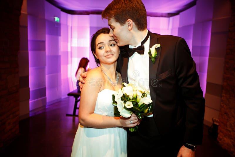 El novio abraza a una novia blanda que se coloca con ella en un restaurante imagen de archivo