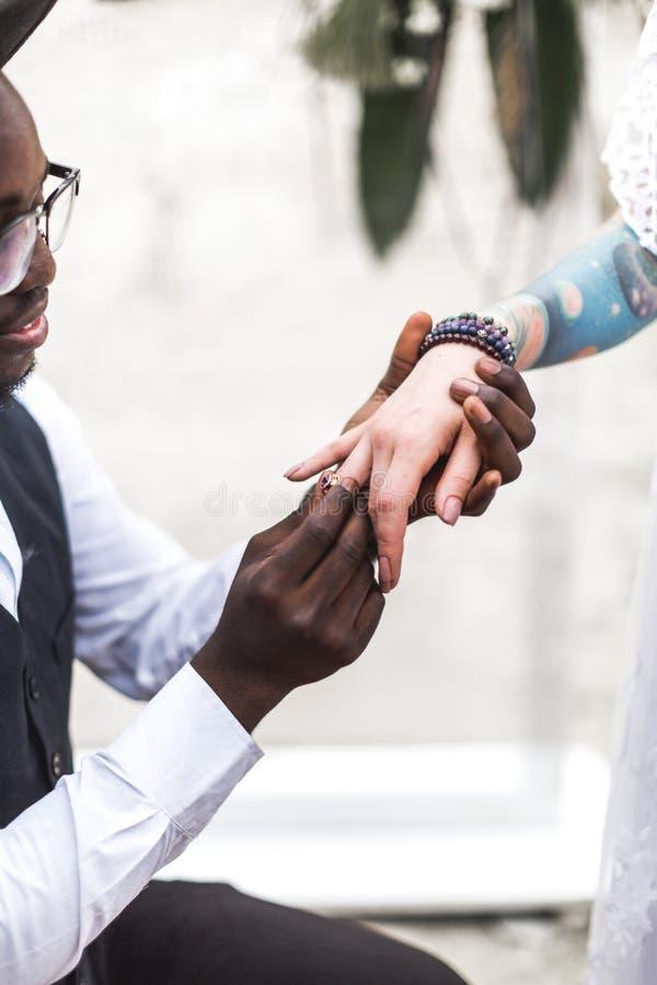 El novio africano lleva el anillo de bodas en el finger de la novia cauc?sica Primer del matrimonio Boda de Boho Estilo de Boho F foto de archivo