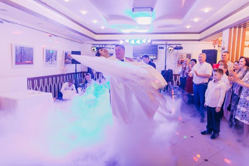 El novio alegre hace girar a la novia de risa durante su primera danza en el restaurante ahumado foto de archivo